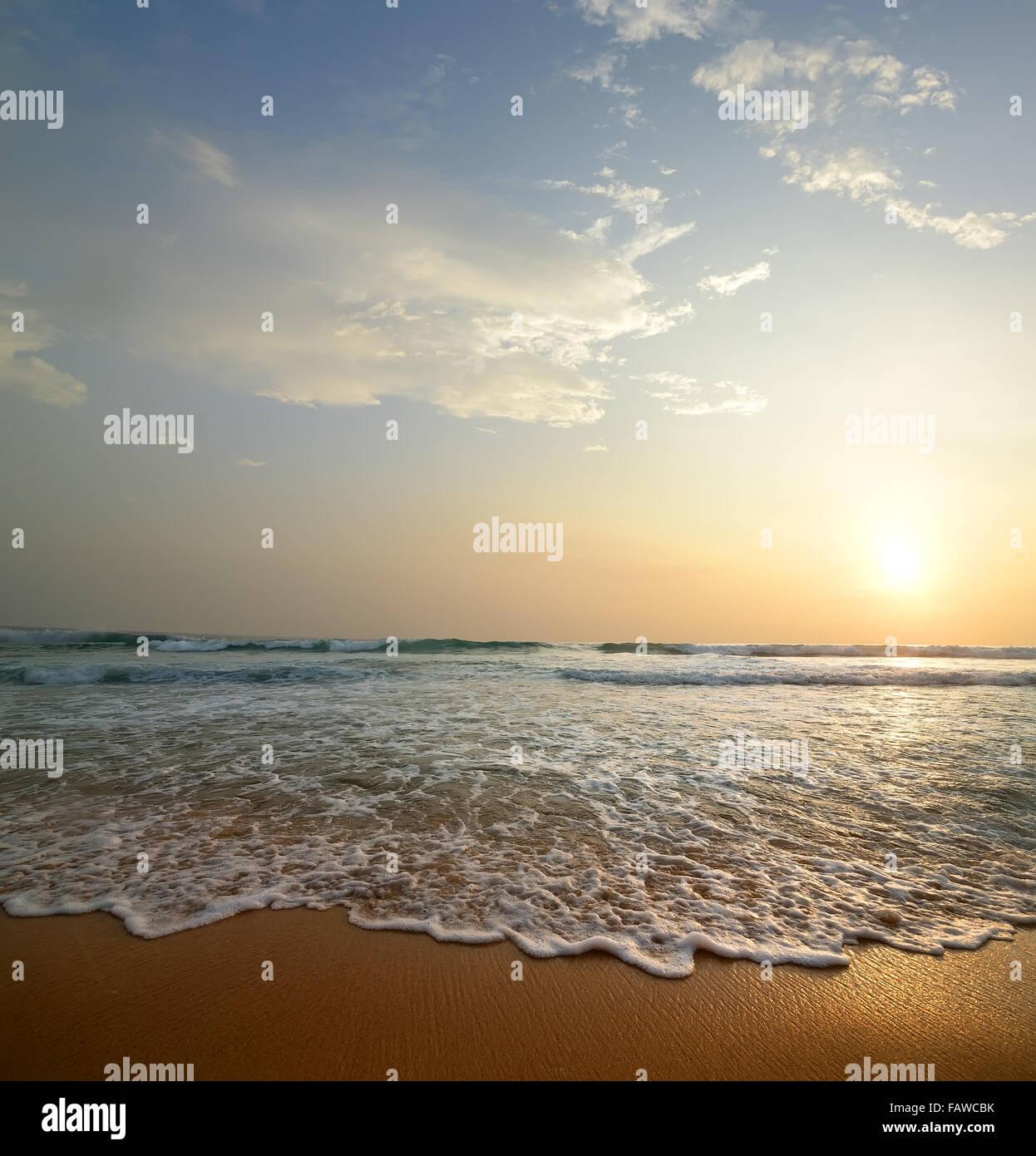 Wellen mit Schaum auf einem sandigen Küste des Ozeans Stockbild