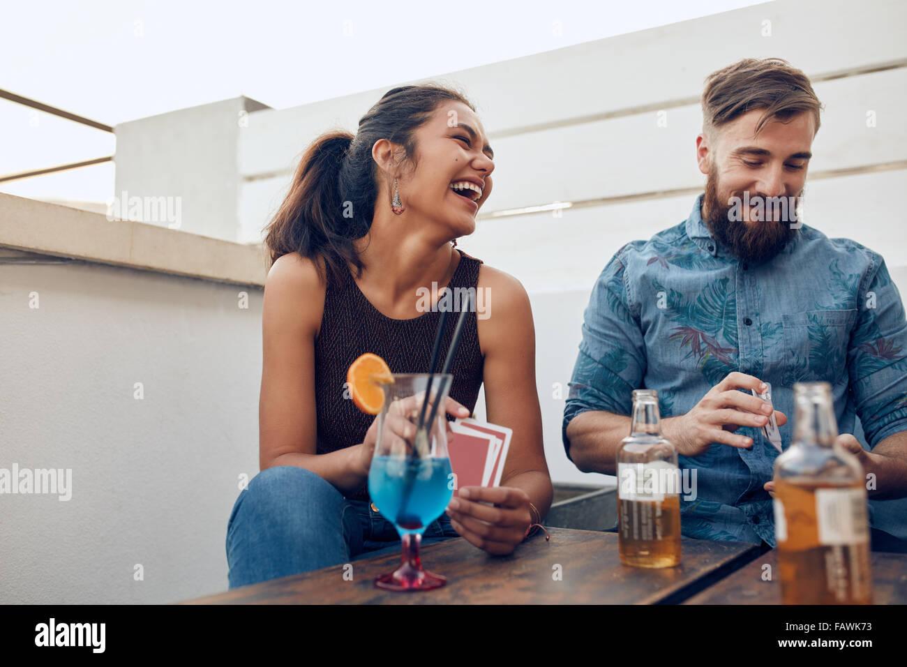 Paar von einem Tisch gefeiert und Spielkarten sitzt. Glückliche junge Mann und Frau Spielkarten während Stockbild