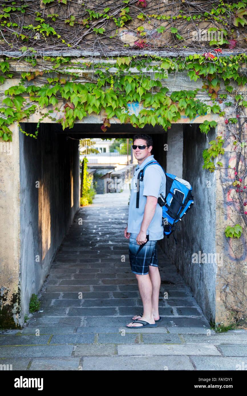 Junge männliche Tourist Rucksack geht unter einem historischen Dorftunnel in Comer See in Sommerkleidung; Varenna, Stockfoto