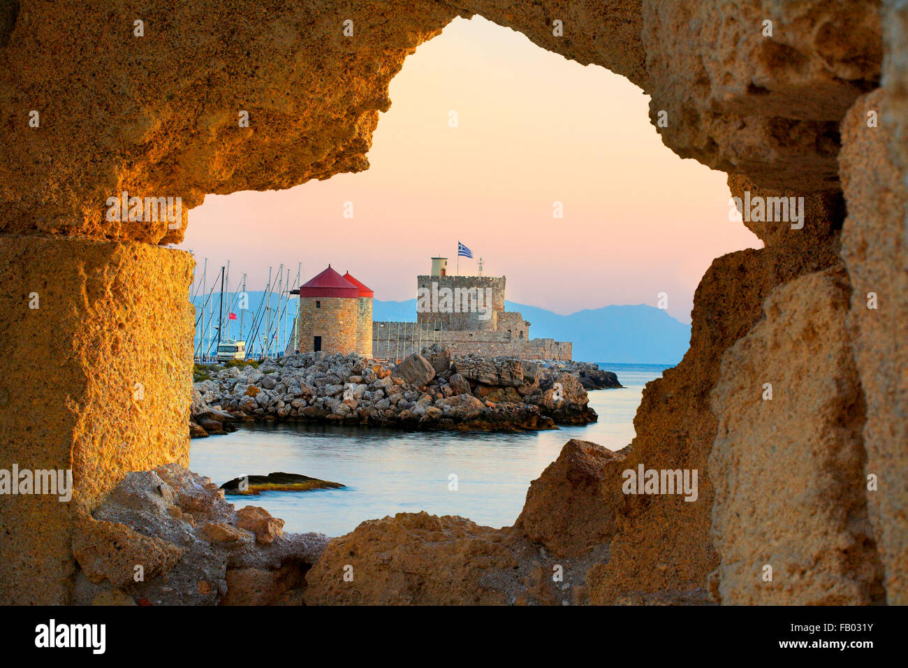 Die Burg und die alten Windmühlen am Eingang zum Hafen von Mandraki in Rhodos, Griechenland, UNESCO Stockbild