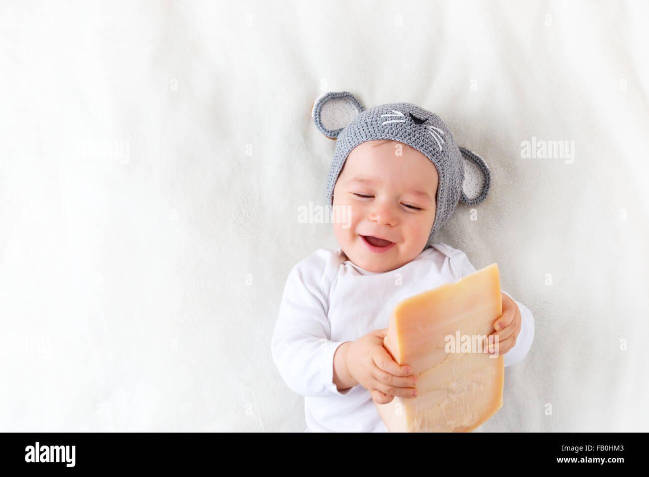 Baby Boy in Maus Hut auf Decke liegend mit Käse Stockbild