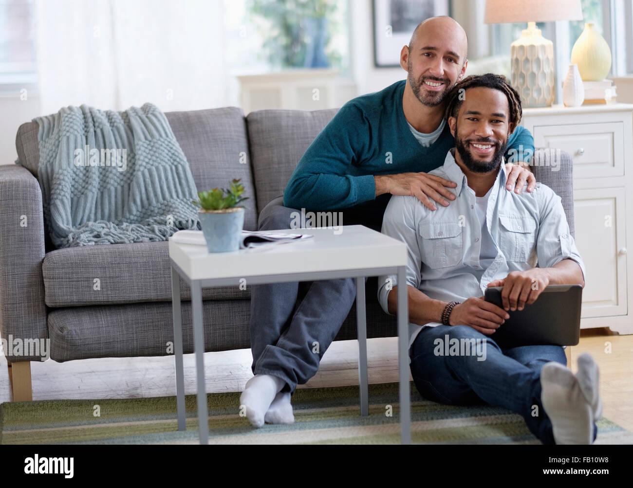 Mann massiert Freund vom Sofa im Wohnzimmer Stockbild