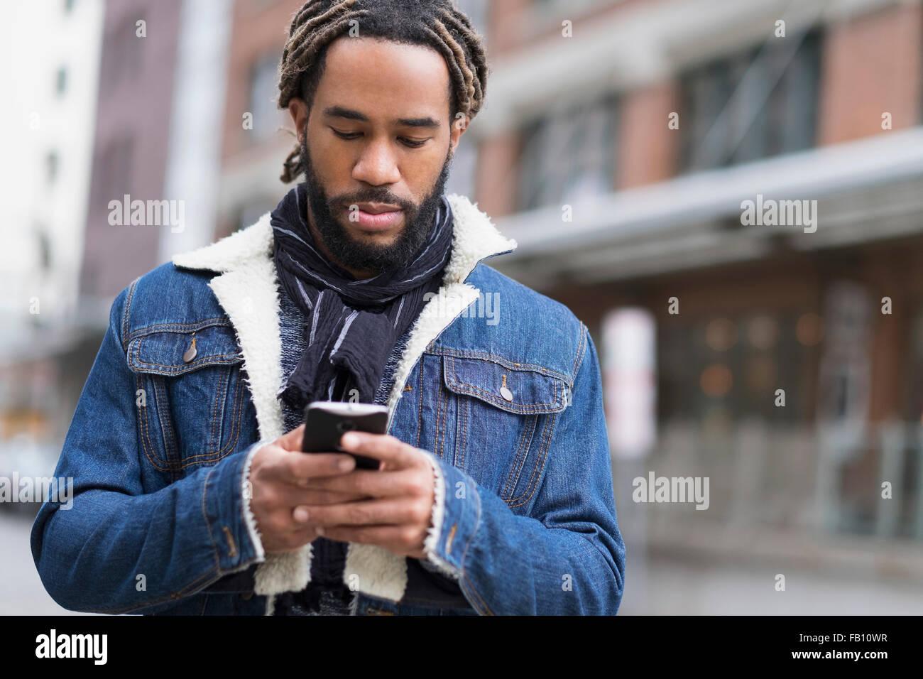 Ernster Mann mit Dreadlocks mit Smartphone in der Straße Stockbild
