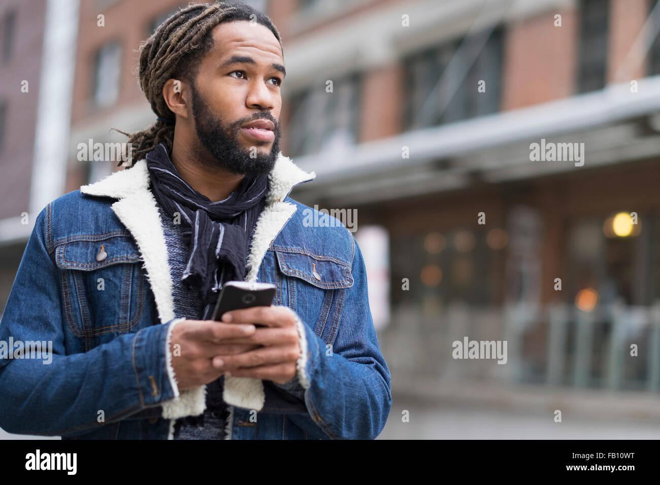 Ernster Mann mit Dreadlocks mit Smartphone in Straße Stockfoto