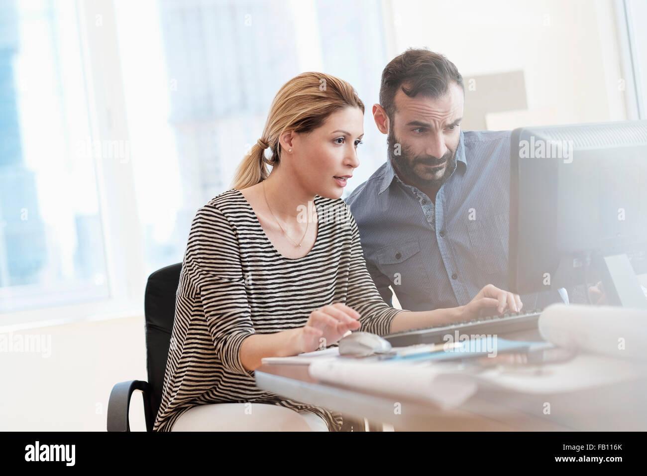 Mann und Frau, die am Computer im Büro Stockbild