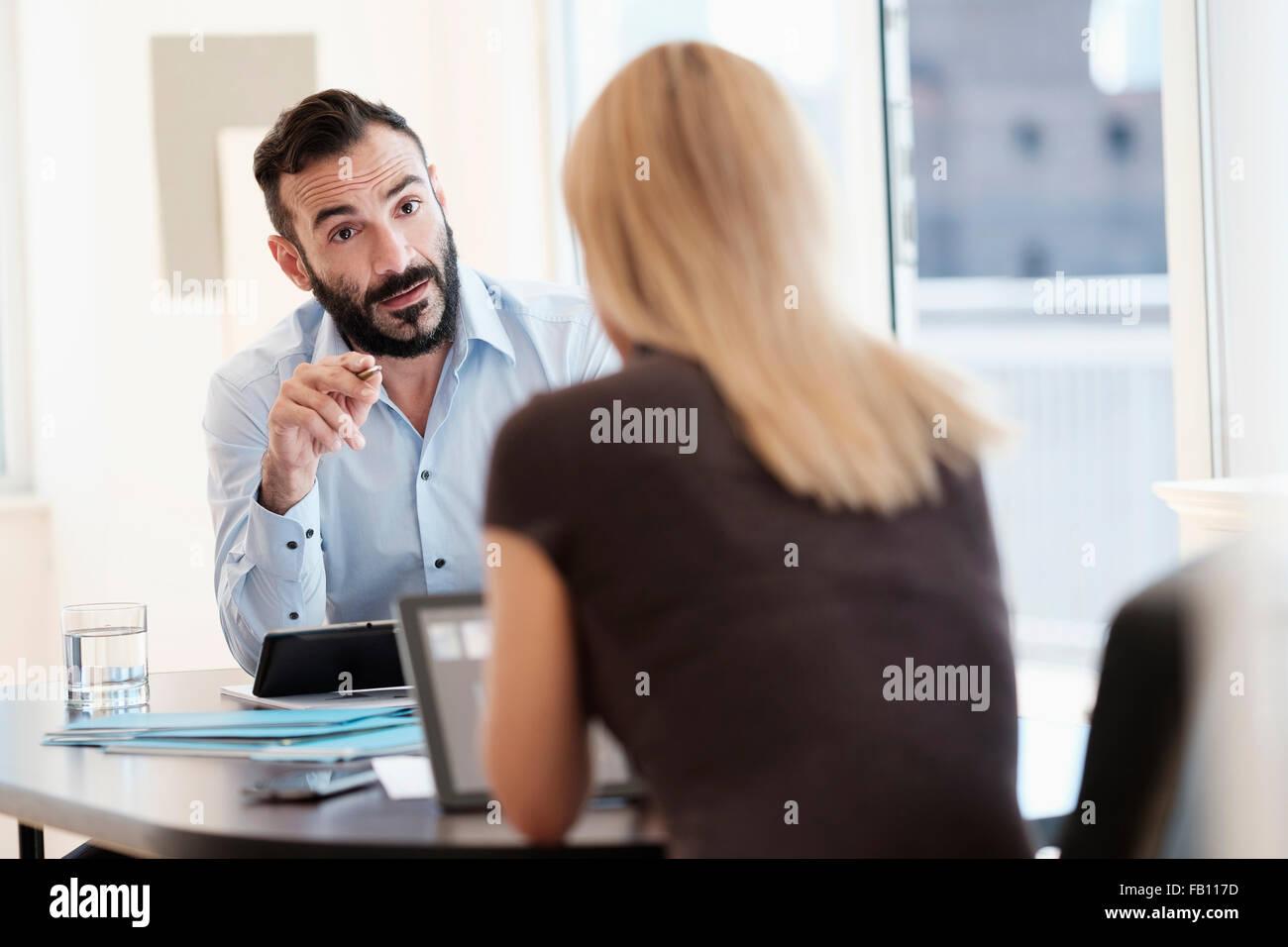 Mann und Frau im Gespräch im Büro Stockbild