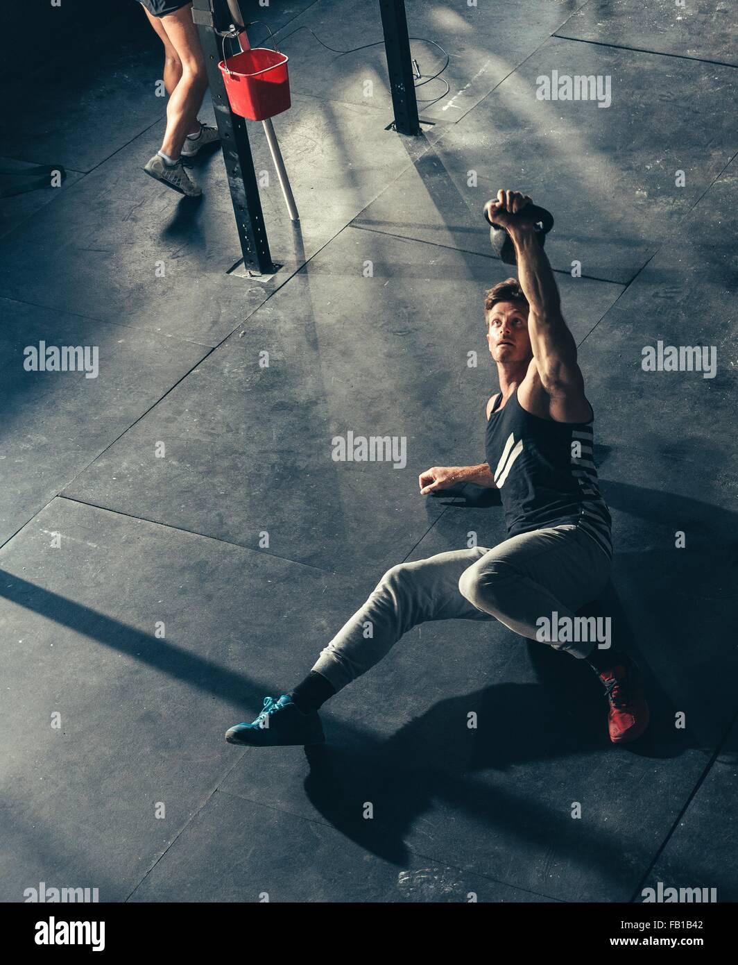 Erhöhte Ansicht des Mannes training mit Kettlebell in Turnhalle Stockbild