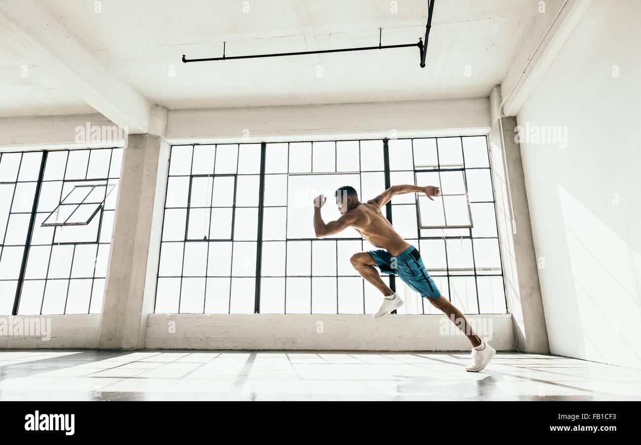 Seitenansicht des Jünglings in Turnhalle leistungsfähige laufende Haltung zu tun Stockbild