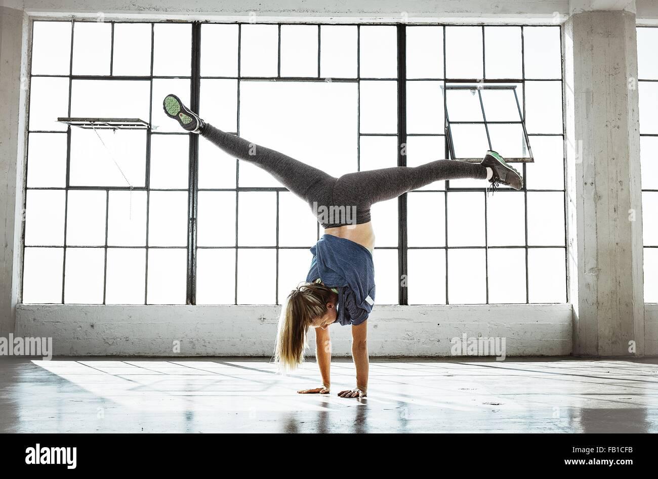 Rückansicht des jungen Frau im Fitnessstudio machen Handstand, offene Beine Stockbild
