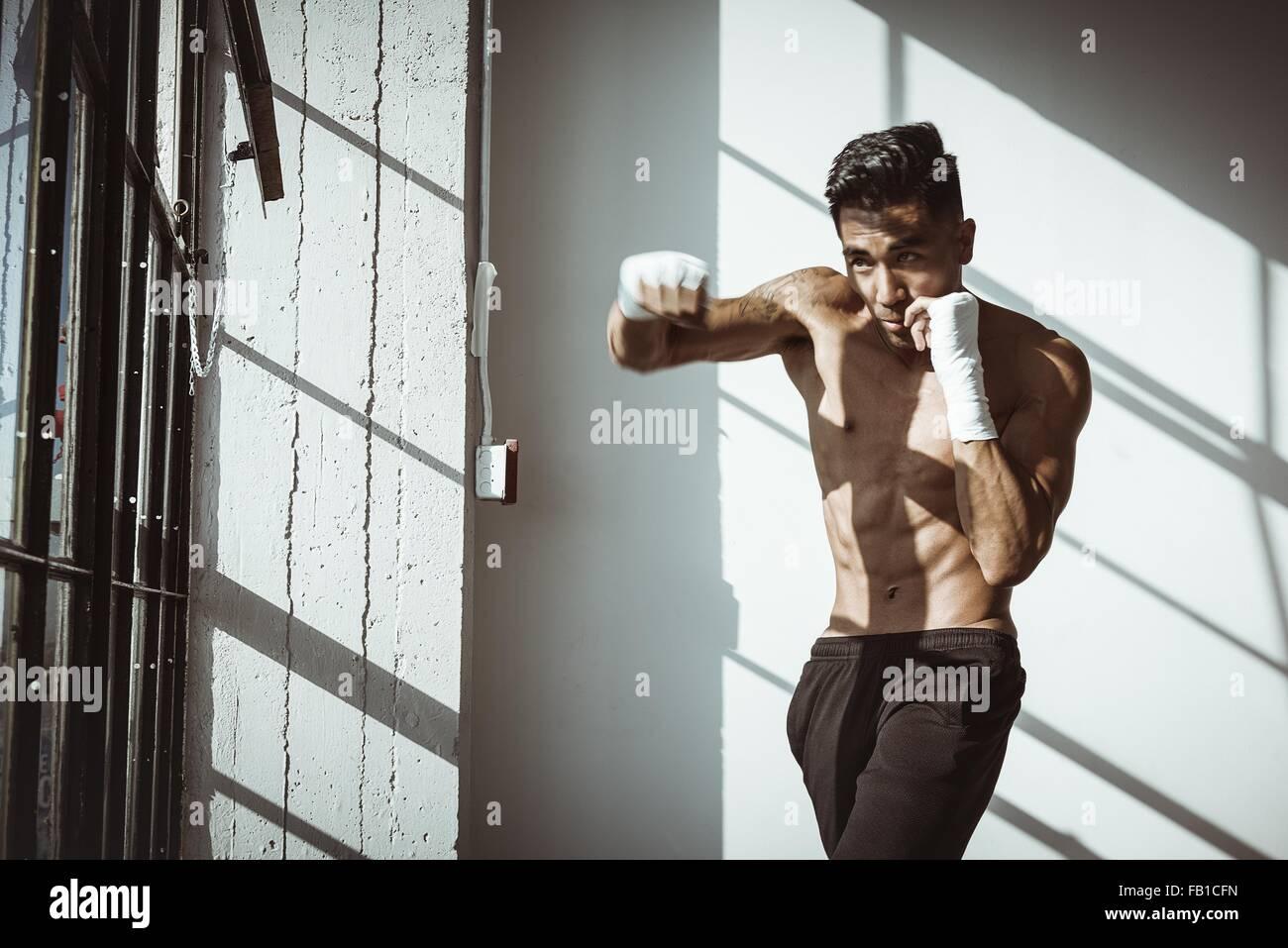 Vorderansicht des Jünglings im Fitness-Studio in Boxen Haltung wegschauen Stockbild