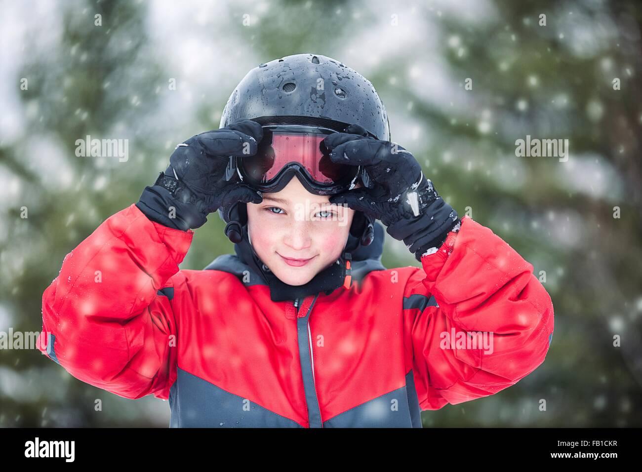 Junge Schutzbrille tragen Helm und Skifahren mit Blick auf die Kamera zu Lächeln, schneit Stockbild