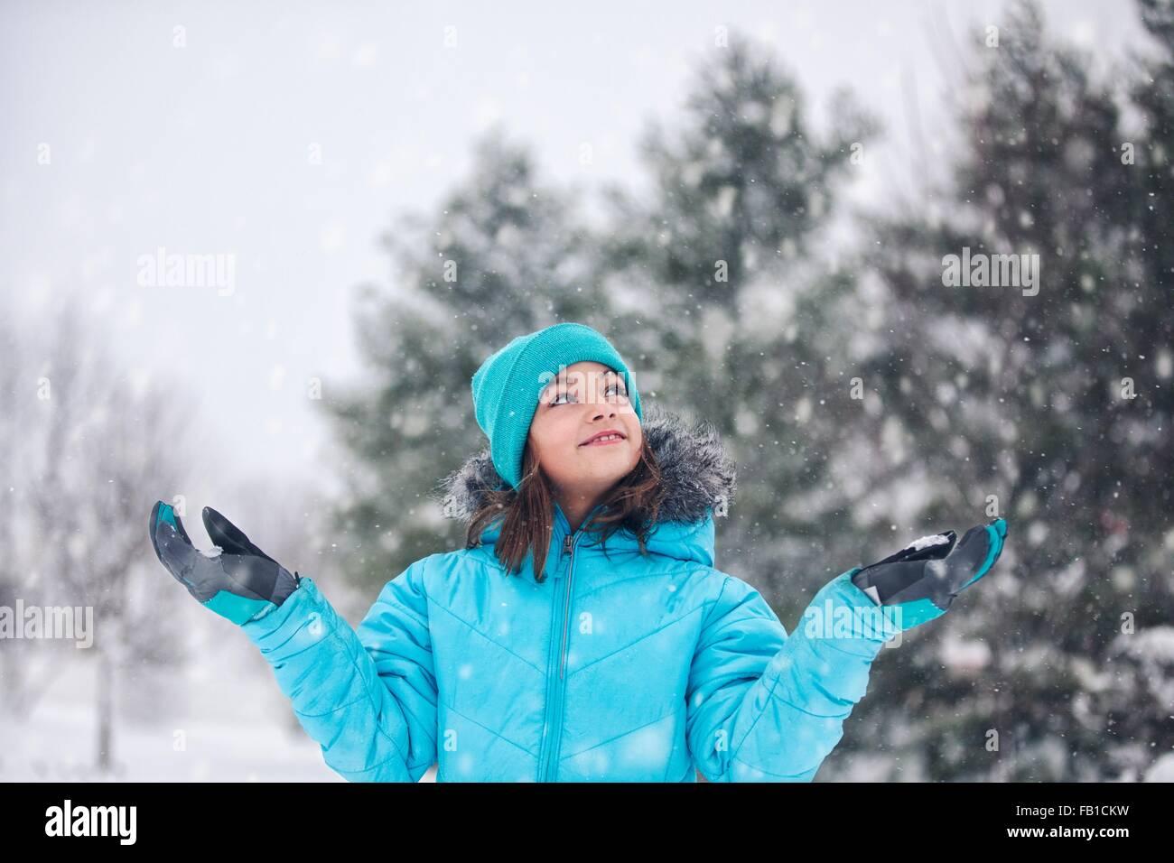 Mädchen tragen Türkis stricken Hut und Mantel, Arme hob, Hände, Schnee, blickte lächelnd zu Stockbild