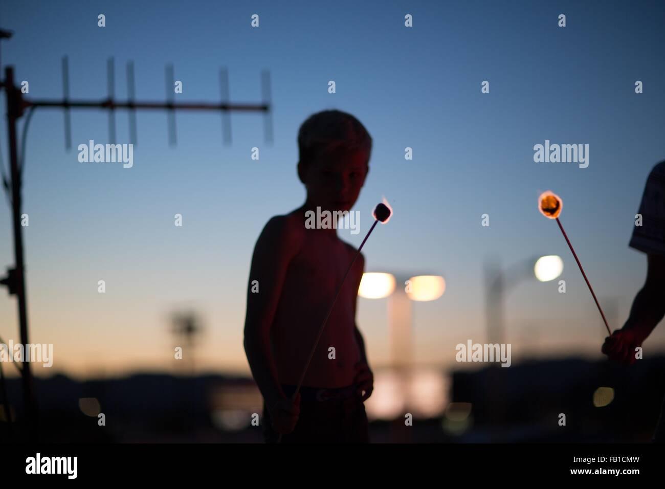 Silhouette der jungen im Teenageralter holding schwelenden Marshmallows auf sticks Stockbild