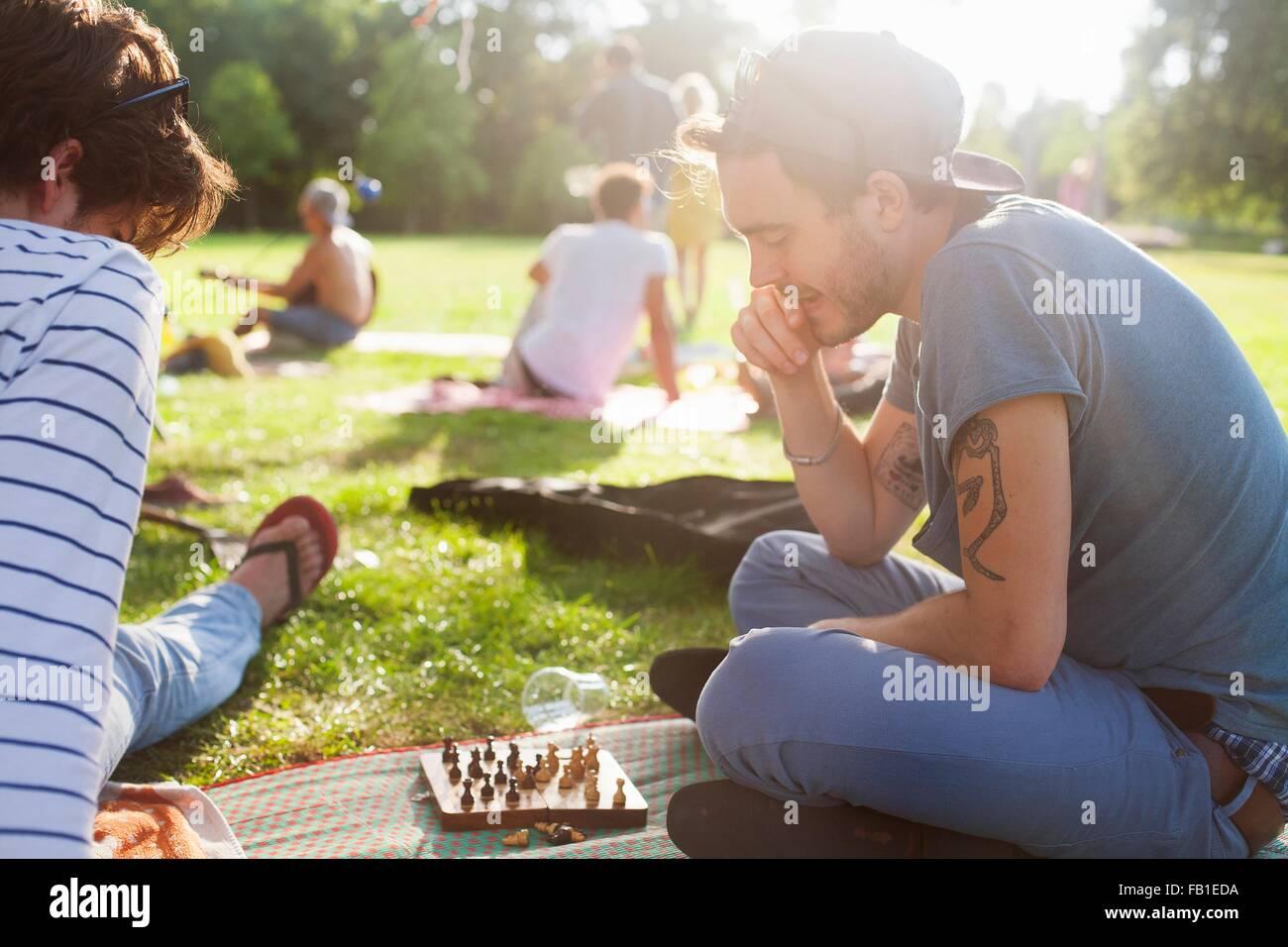 Junge Erwachsene Brettspiel auf sunset Party im park Stockbild