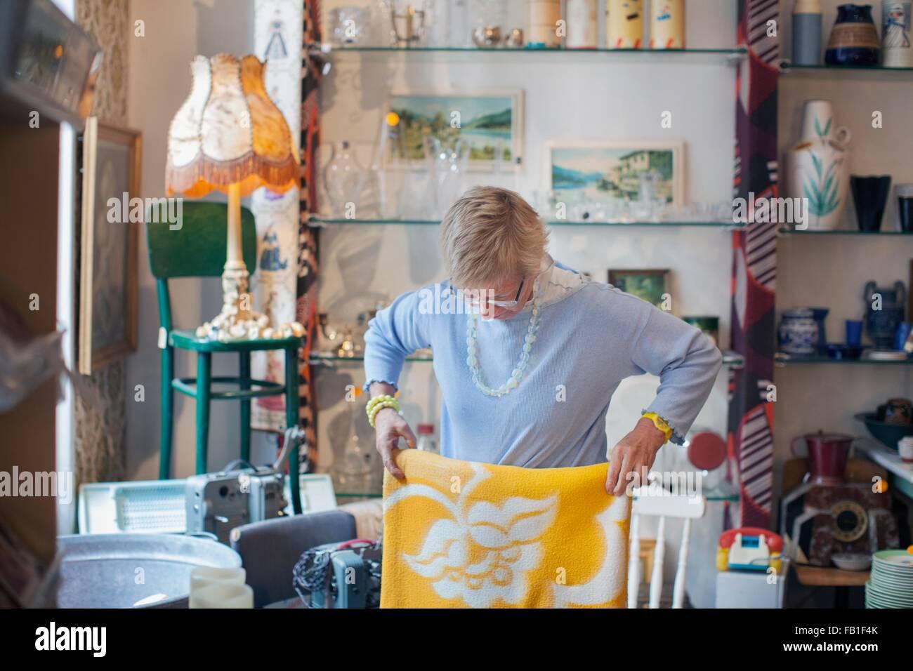 Reife Frau Faltung gelbe Decke in Vintage-shop Stockbild
