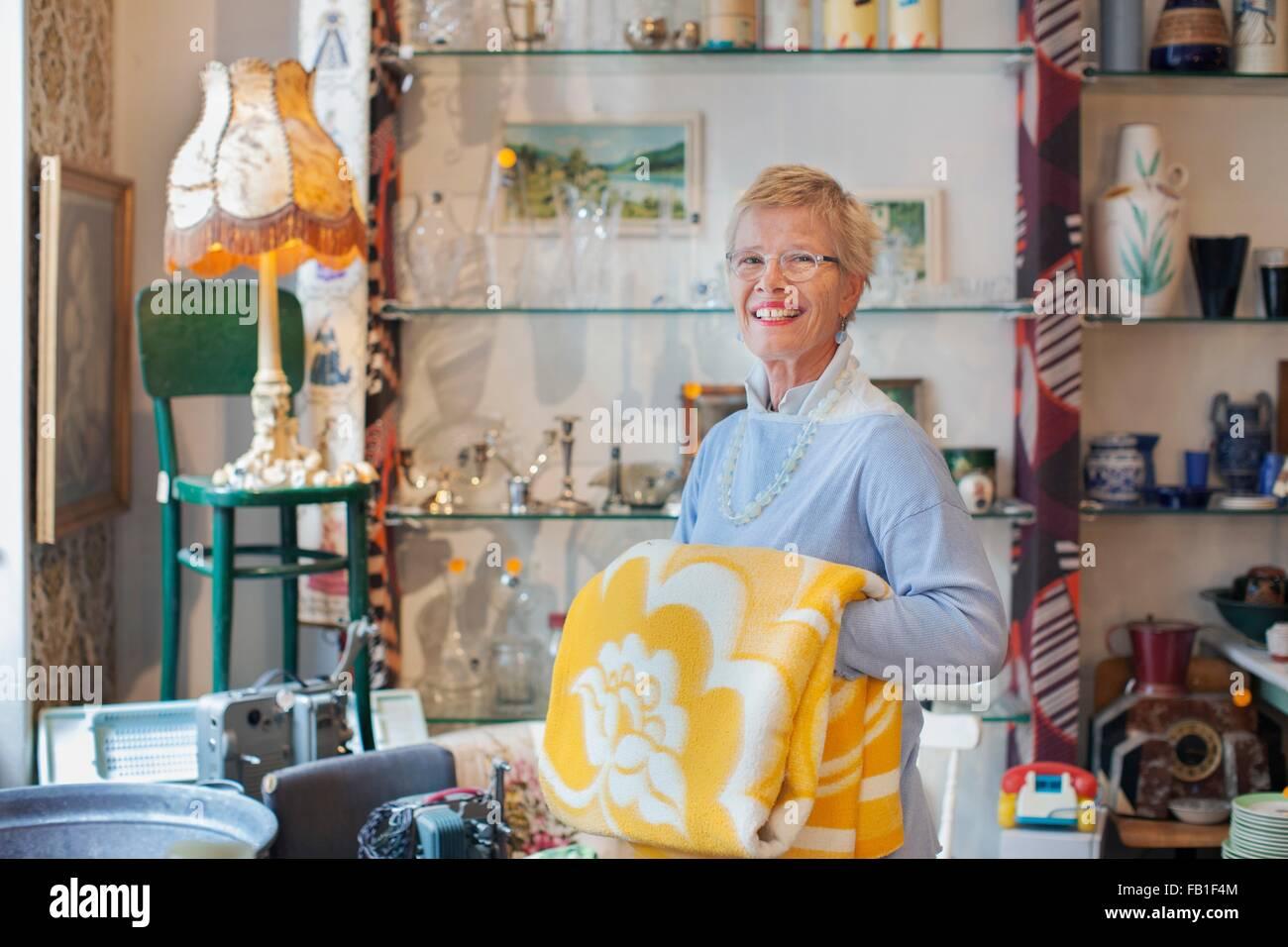 Porträt von Reife Frau Faltung gelbe Decke in Vintage-shop Stockbild