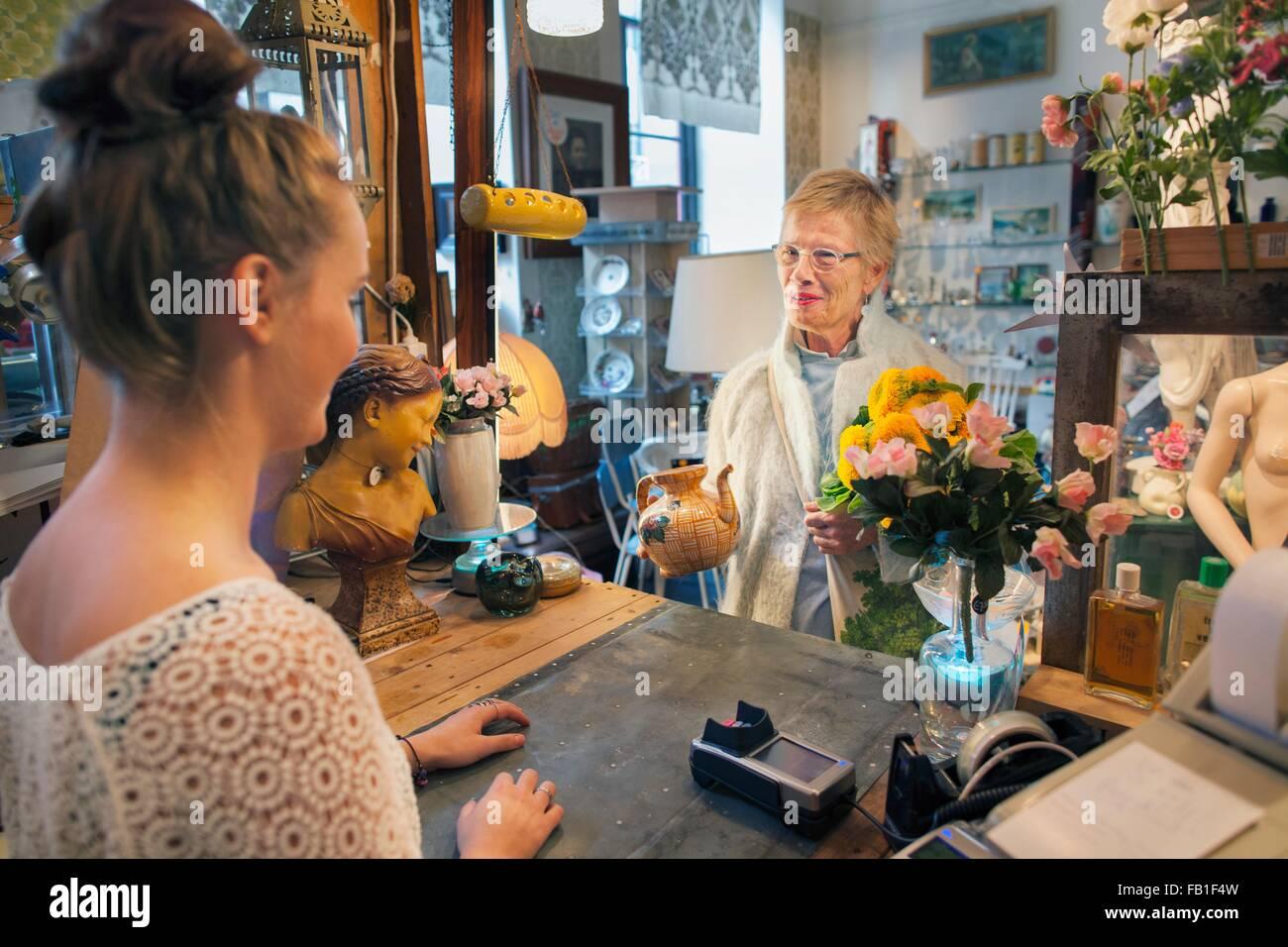 Ältere Kundin Teekanne in Vintage-Shop kaufen Stockbild