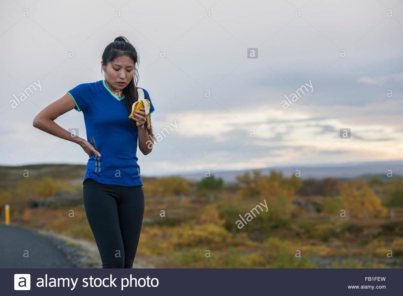 Mitte Erwachsene Frau Pause eine von Übung, Banane, unterwegs in ländlichen Landschaft Essen Stockbild