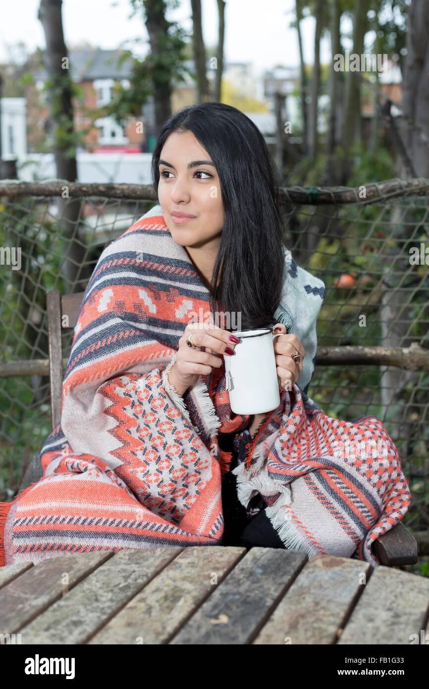 Junge Frau eingewickelt in Decke, Kaffeetrinken, Hampstead Heath, London Stockfoto