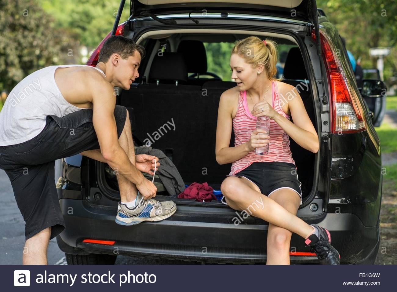 Junges Paar sitzt auf der Rückseite der Großraumwagen, Vorbereitung der Wanderung Stockbild
