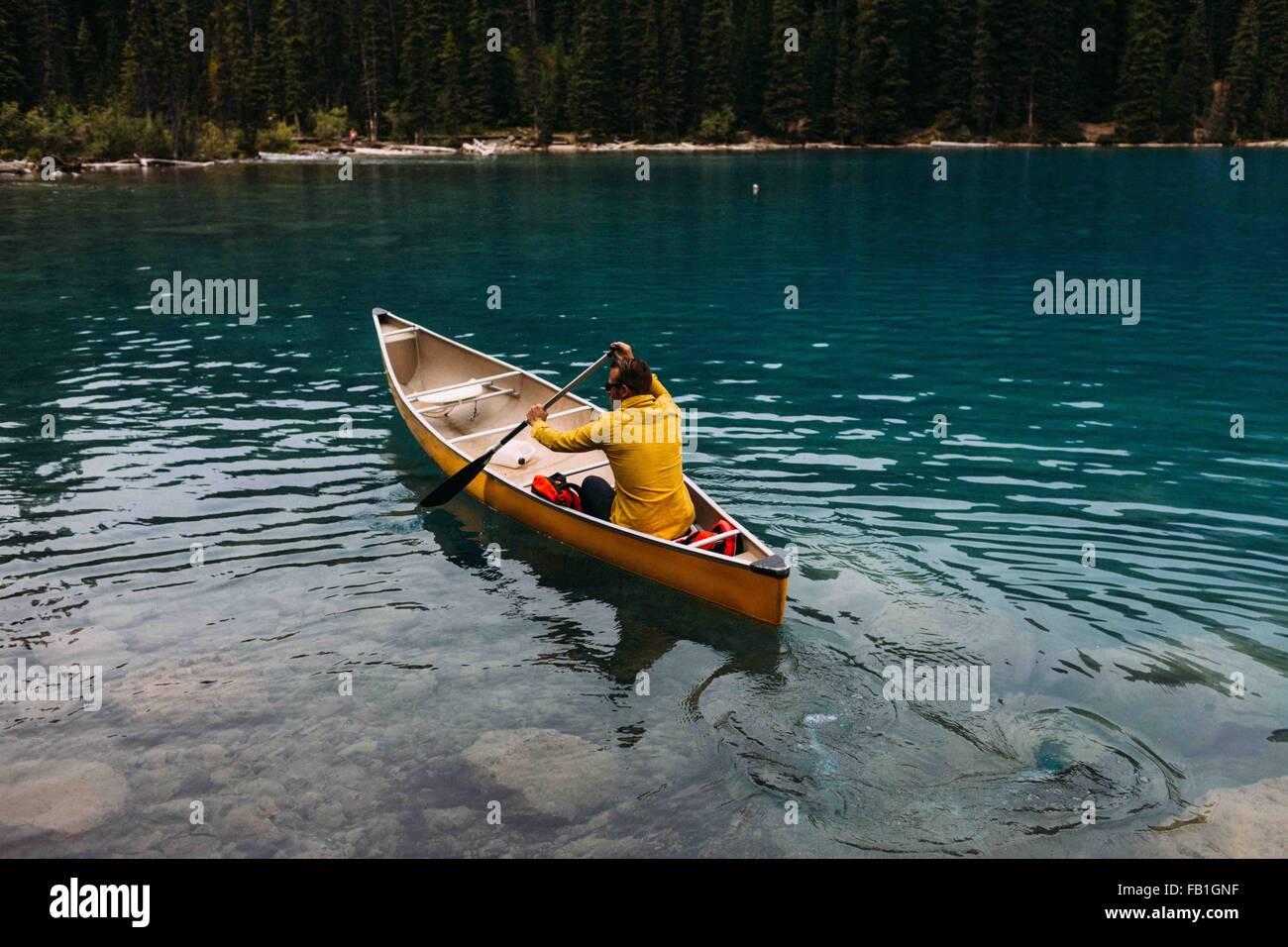 Hohen Winkel Rückansicht Mitte erwachsenen Mannes paddeln Kanu auf Moraine Lake, Banff Nationalpark, Alberta Stockbild