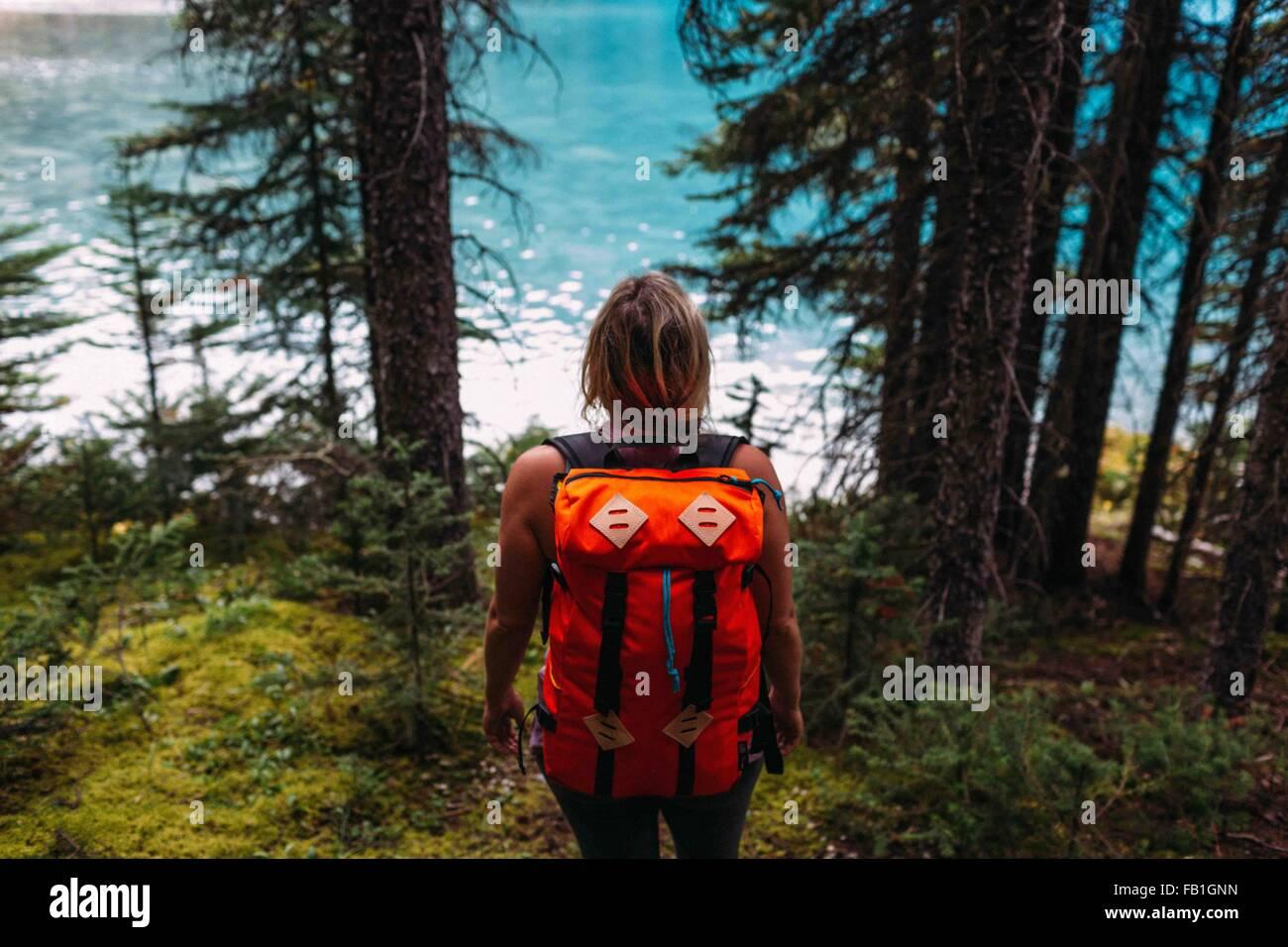 Rückansicht Mitte Erwachsene Frau, die die Farbe orange Rucksack Wald Wasser Moraine Lake Banff Nationalpark Alberta Stockfoto