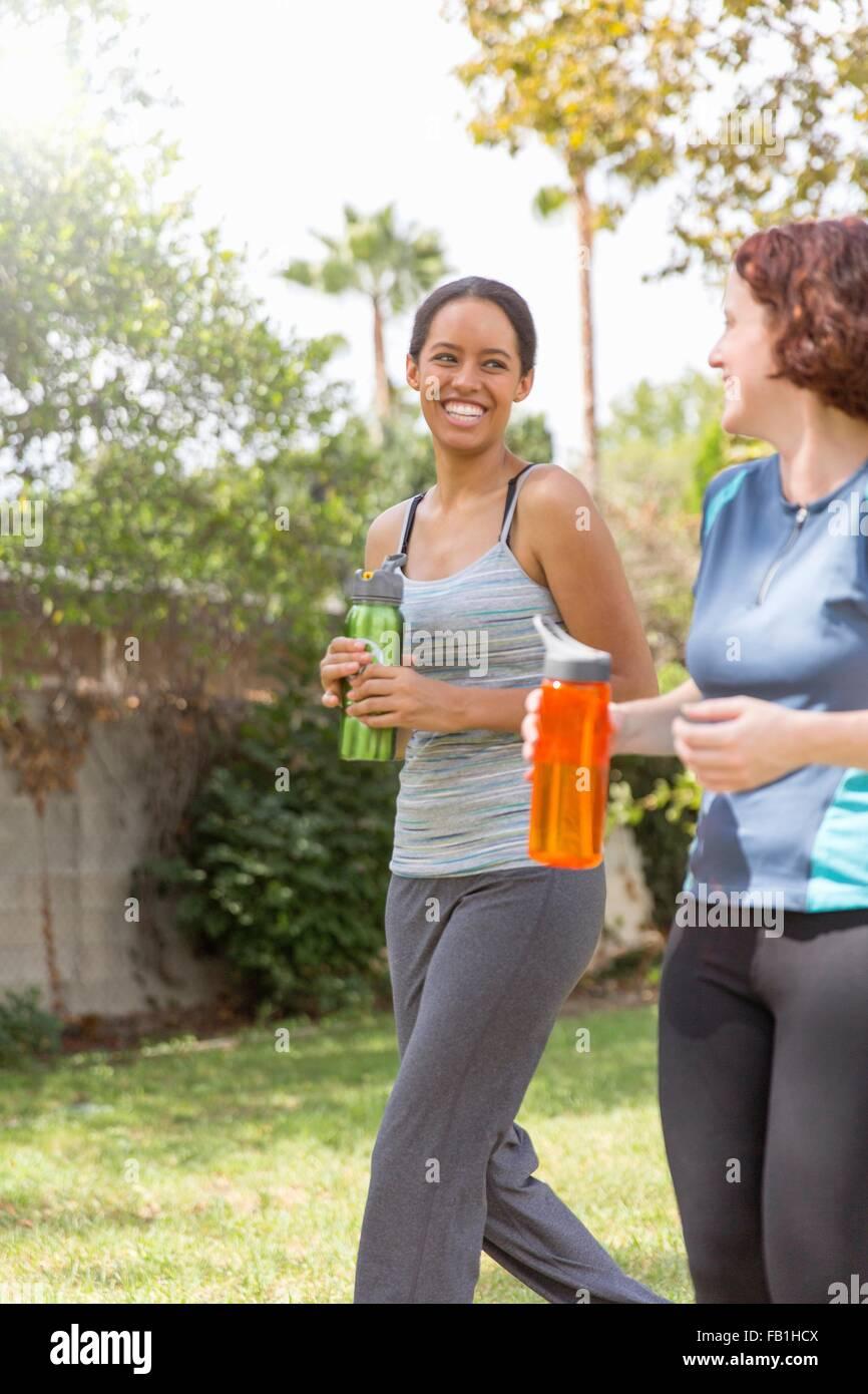 Junge Frauen spazieren tragen Sportbekleidung mit Wasserflaschen, lachen Stockbild