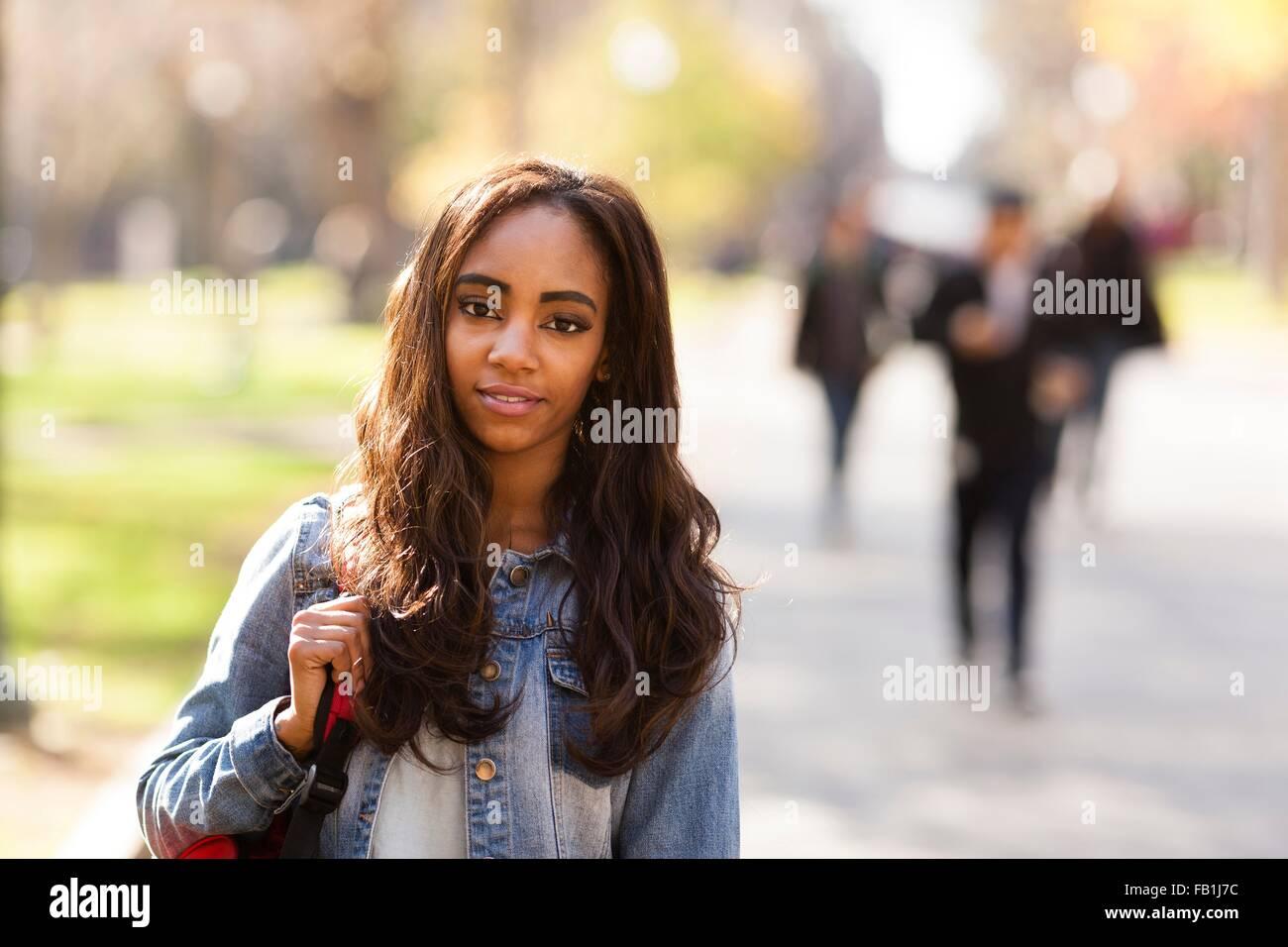 Porträt der jungen Frau mit langen braunen Haaren tragen Jeansjacke, Blick auf die Kamera zu Lächeln Stockbild