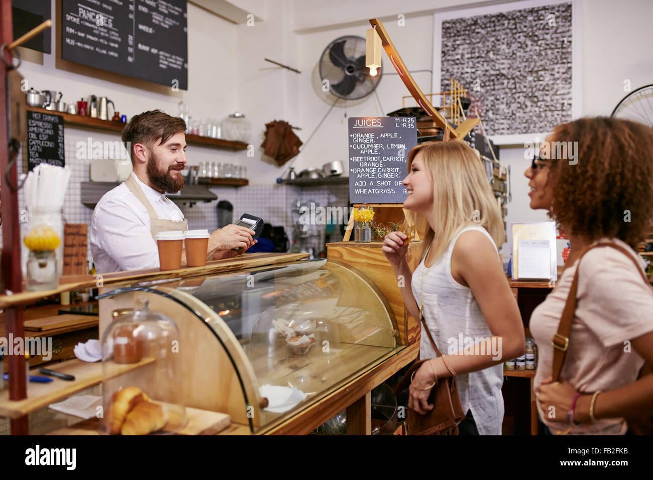 3119d70bbb4246 Schuss von einem jungen Frauen Freunde eine Bestellung in einem Café.  Kellner