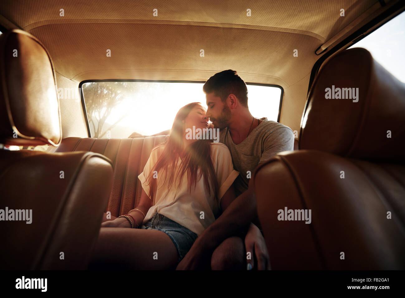 Romantische junges Paar auf Rücksitz des Autos. Liebespaar auf Roadtrip. Stockbild