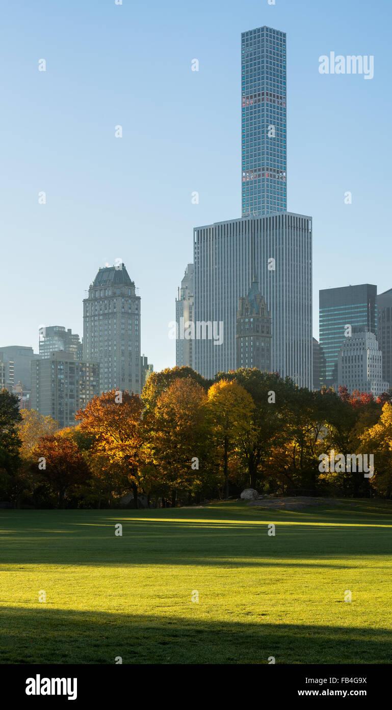 Herbst Sonnenaufgang in Sheep Meadow Central Park mit Blick auf Midtown Manhattan Wolkenkratzer, einschließlich Stockbild