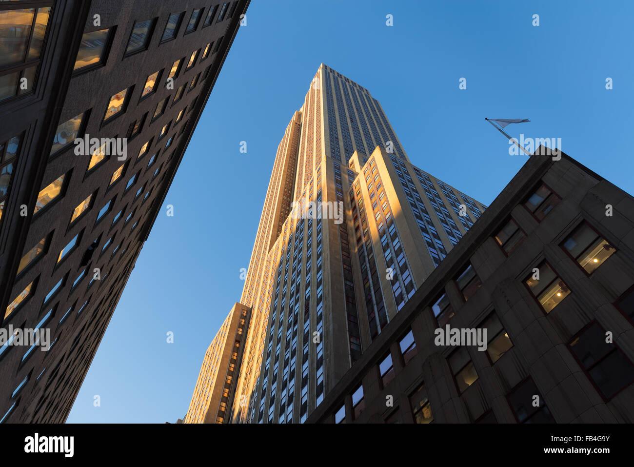Empire State Building bei Sonnenuntergang von unten. Niedrigen Winkel auf der Art-Déco-Wolkenkratzer befindet Stockbild