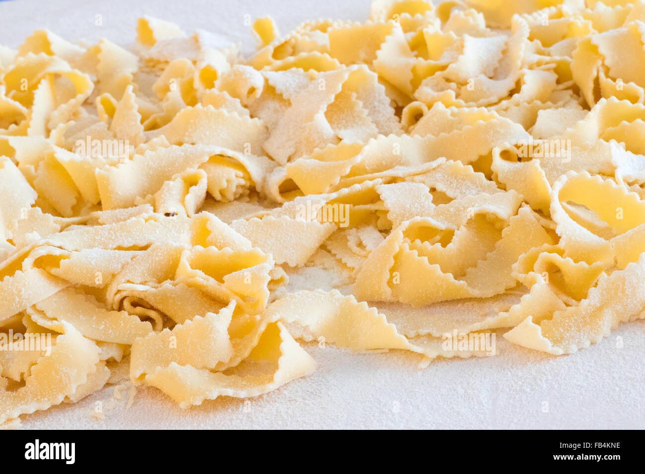 """Handgemachte italienische Pasta, sind Ginelle"""" genannt, auf Holzbrett mit Mehl. Stockbild"""