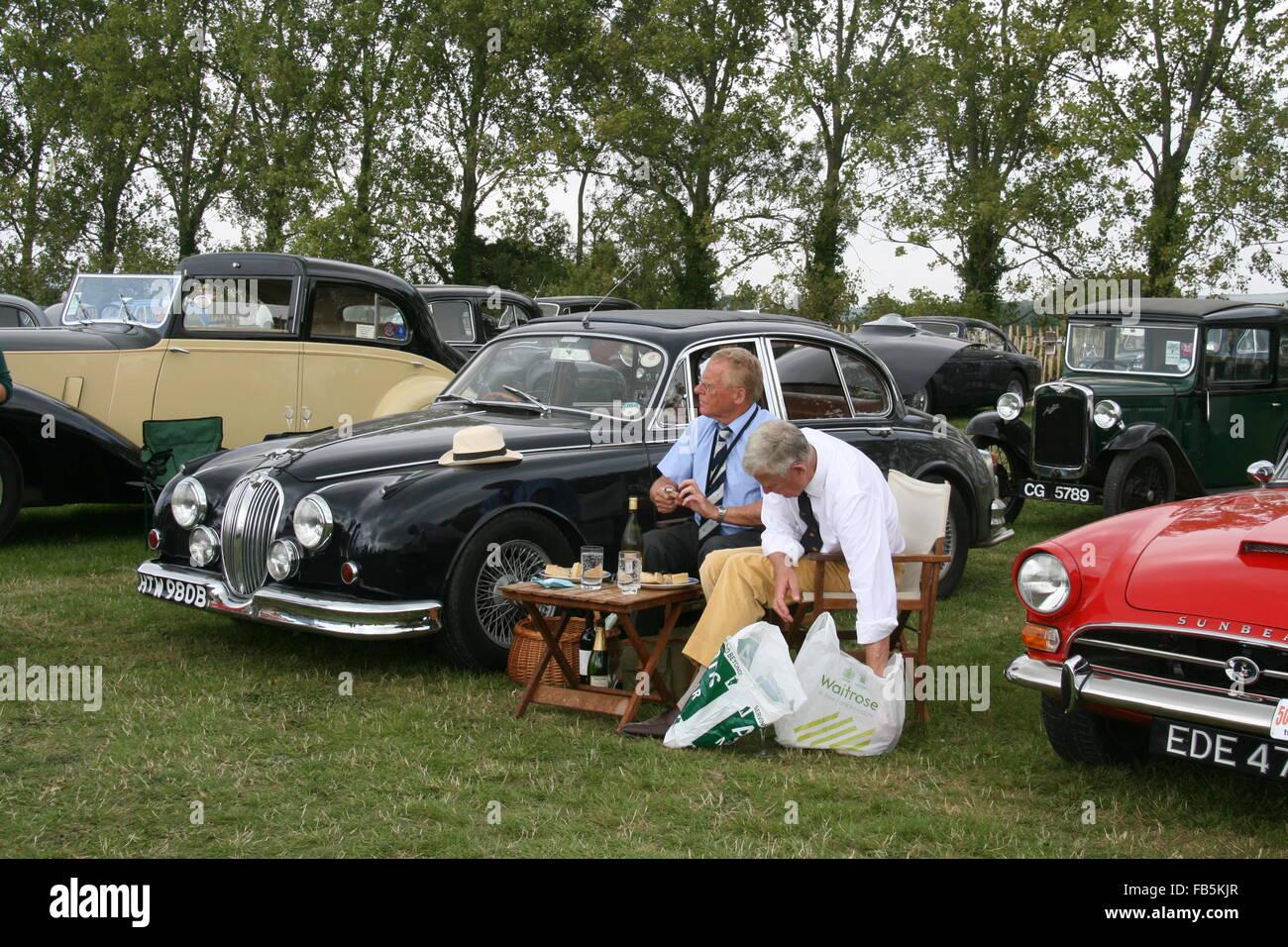Besucher mit einem Picknick unter den klassischen Autos beim Goodwood Revival Stockbild