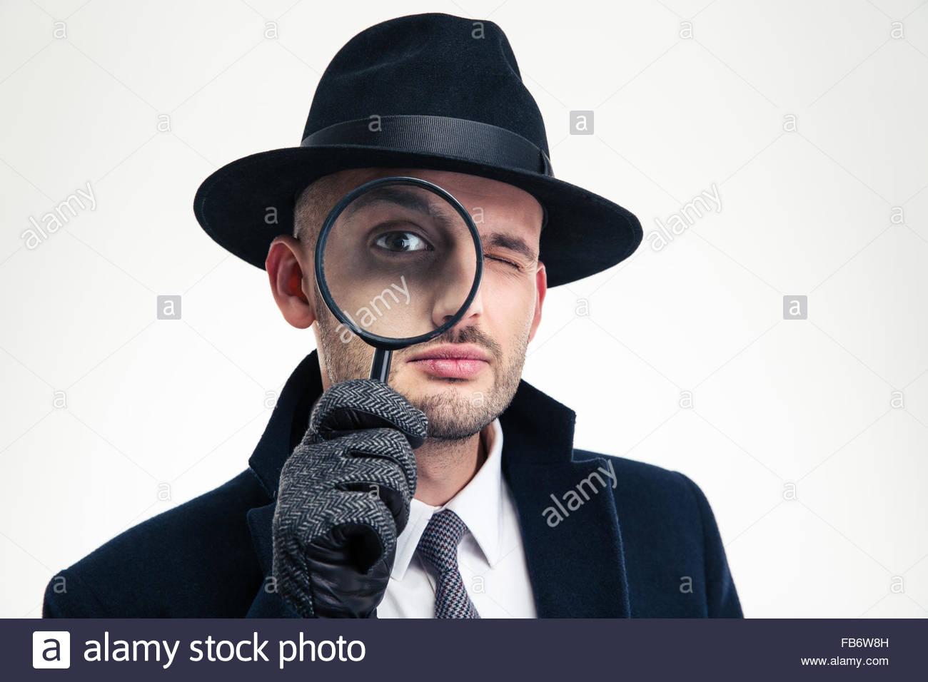 Lustige konzentrierte Inspektor in schwarzen Hut, Mantel und Handschuhe Blick durch die Lupe auf weißem Hintergrund Stockbild