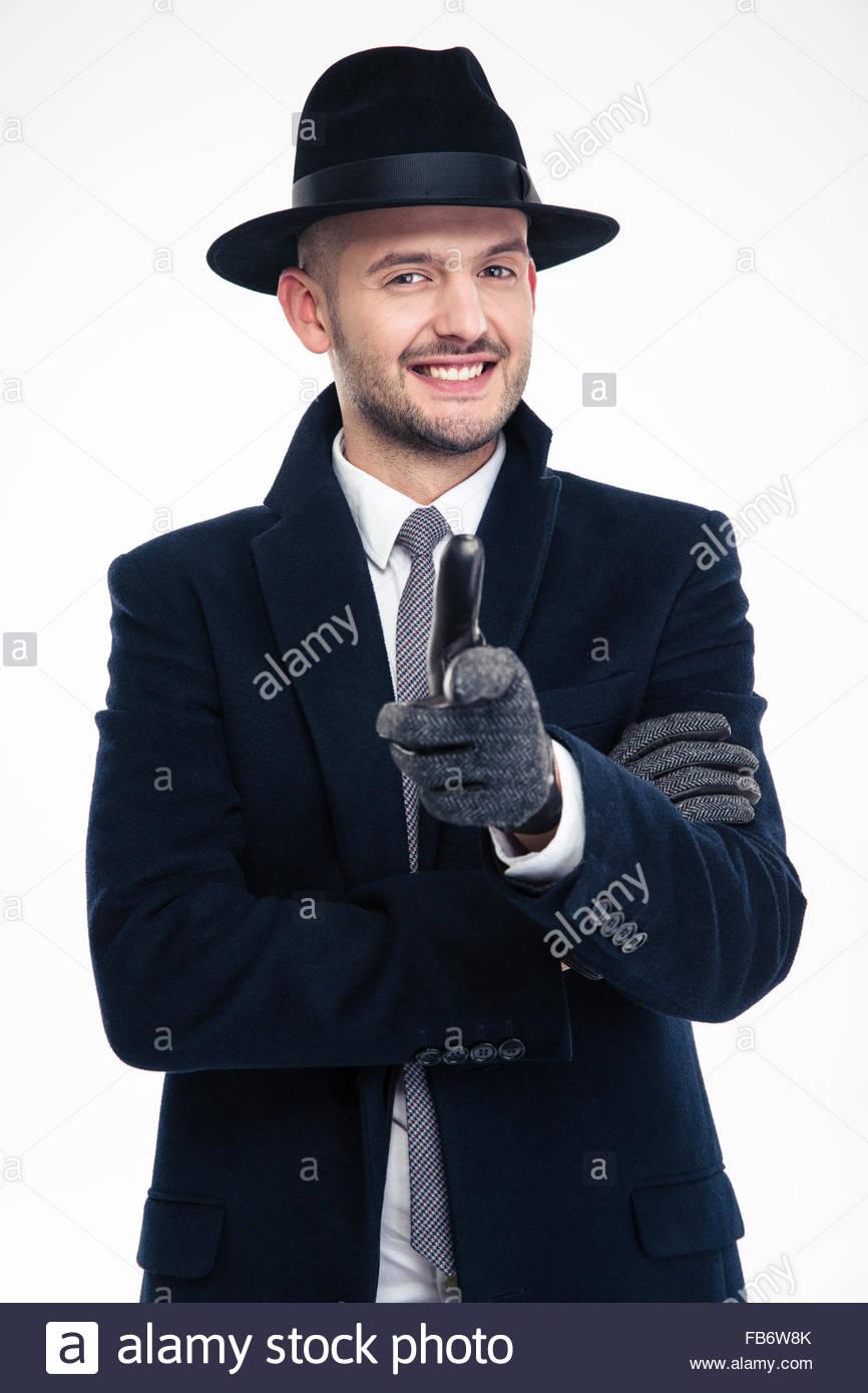 Fröhliche gut aussehend Ermittler in schwarzen Mantel, Mütze und Handschuhe, zeigen Sie auf weißem Stockbild