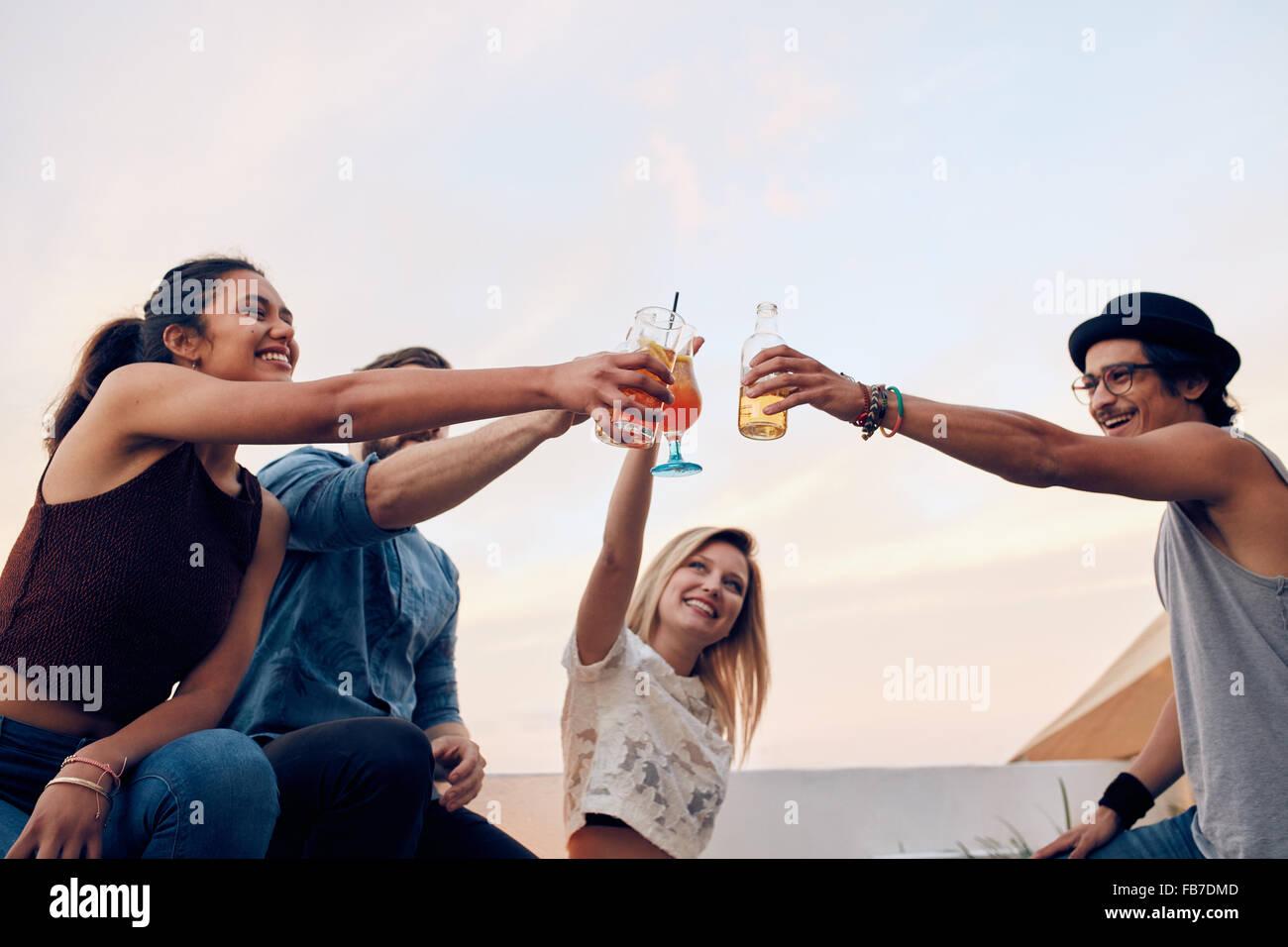 Glückliche Freunde feiern den Erfolg mit einem Toast auf Party auf dem Dach. Junge Männer und Frauen Toasten Stockbild