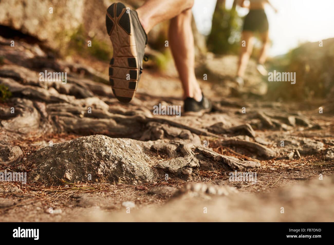 Querfeldein laufen. Nahaufnahme der männliche Füße laufen durch felsiges Gelände. Fokus auf Stockbild