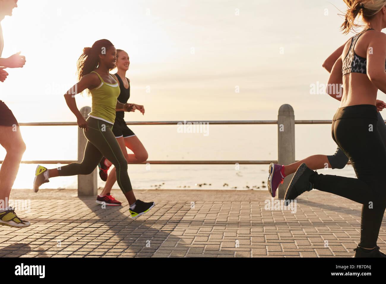 Junge Frau mit Freunden auf der Promenade am Meer bei Sonnenuntergang ausgeführt. Passen Sie junge Leute laufen Stockbild