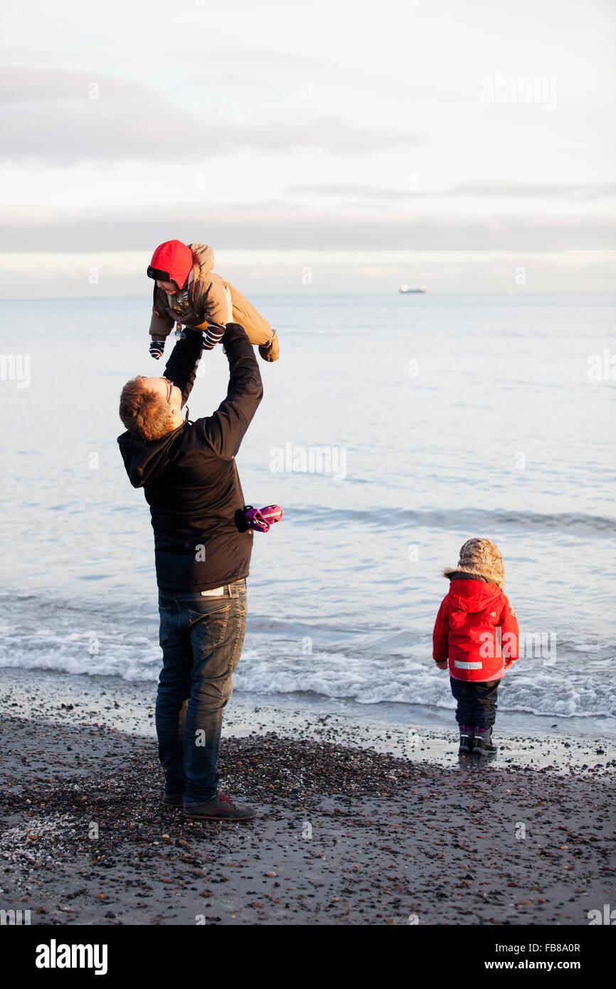Dänemark, Grenen, Vater mit Töchtern (6-11 Monate) (2-3) spielen am Strand Stockfoto
