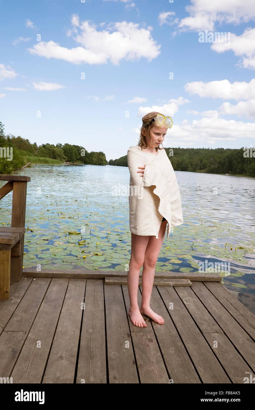 Schweden, Stockholm, Nacka, Sicklasjon, See Sickla Mädchen (10-11) gewickelt im Handtuch stehen auf hölzernen Stockbild