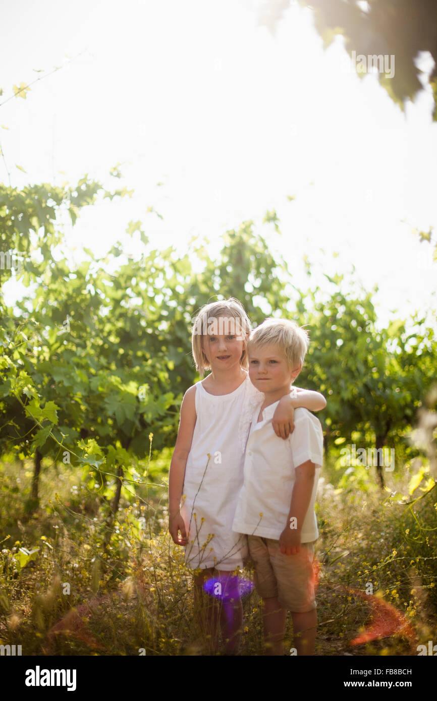 Italien, Toskana, Porträt der Schwester (6-7) umarmen jüngerer Bruder im Obstgarten (4-5) Stockfoto