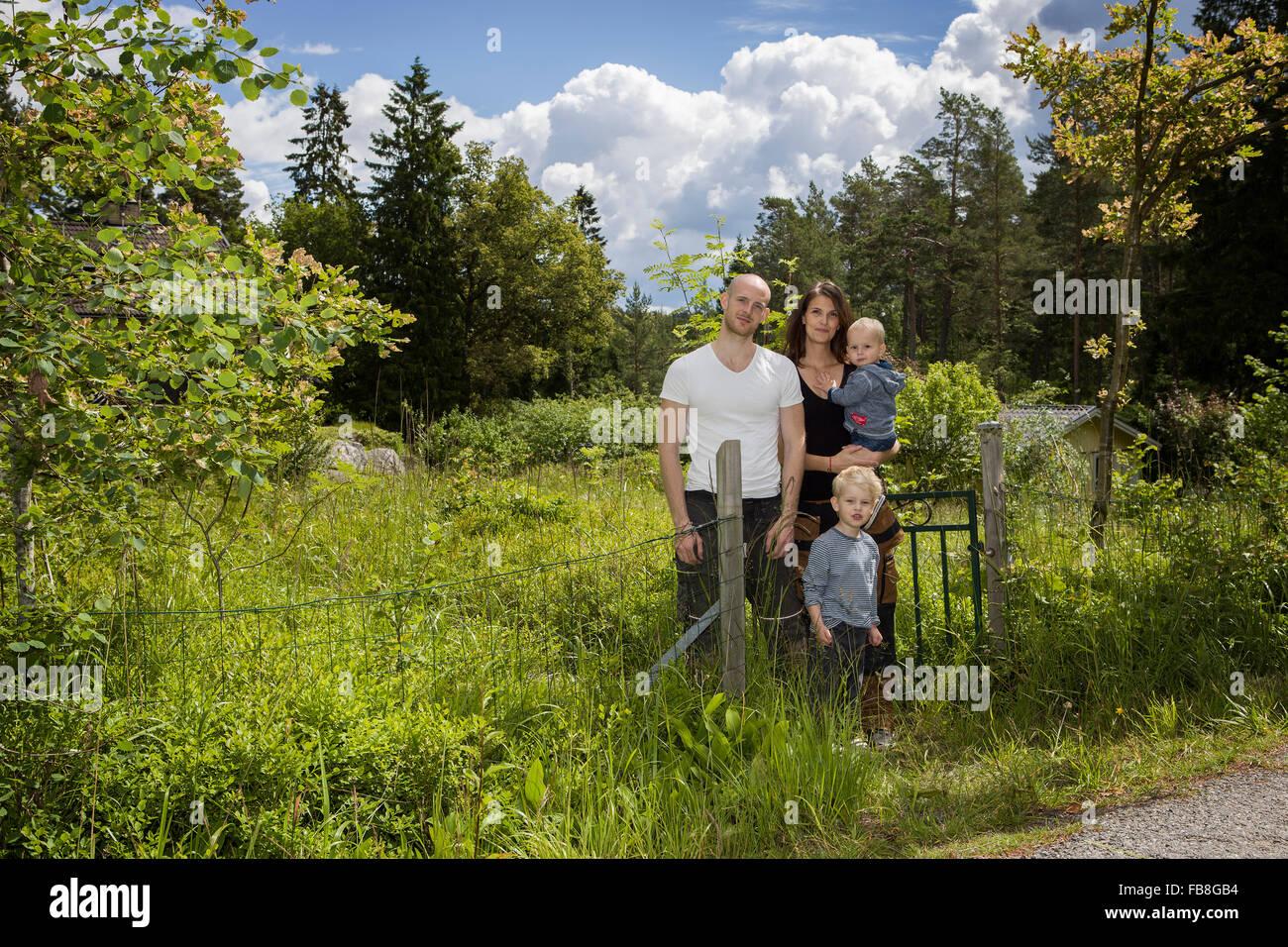 Schweden, Stockholm, Uppland, Nacka, Familie mit zwei Kindern (18-23 Monate, 4-5) stehen unter üppigem Grün Stockbild