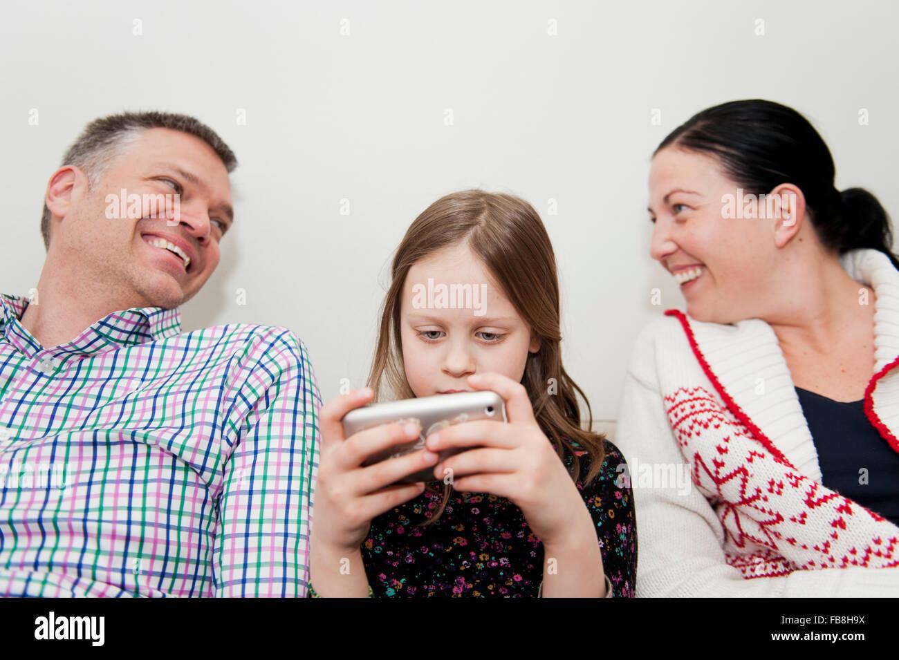 Mädchen (8-9) und Eltern SMS auf sofa Stockfoto