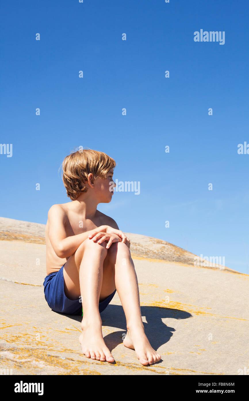 Schweden, Uppland, Runmaro, Barrskar, junge (6-7) sitzt auf Felsen im Sommer Stockbild