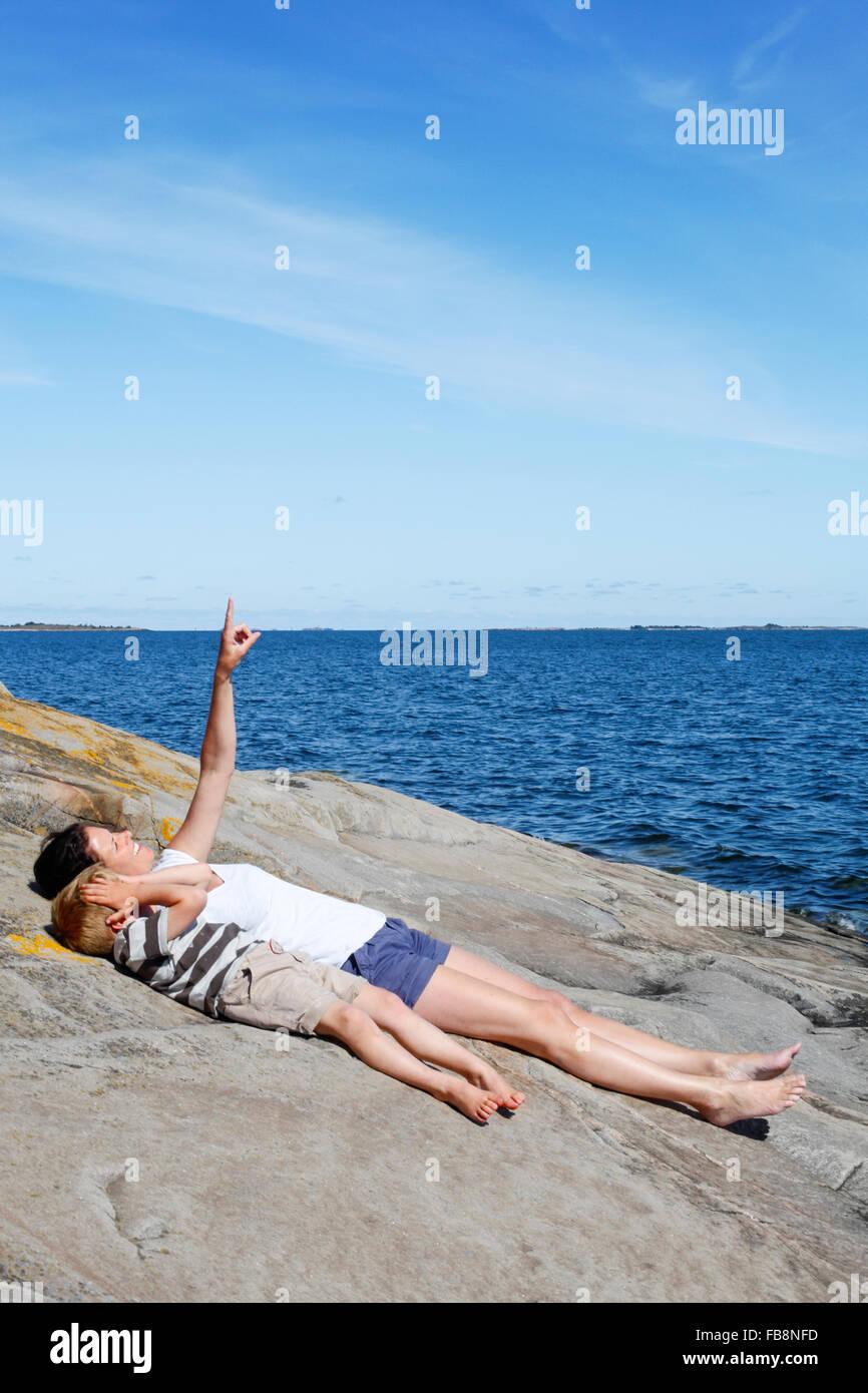 Schweden, Uppland, Runmaro, Barrskar, Mutter mit Sohn (4-5) liegen direkt am Meer Stockbild