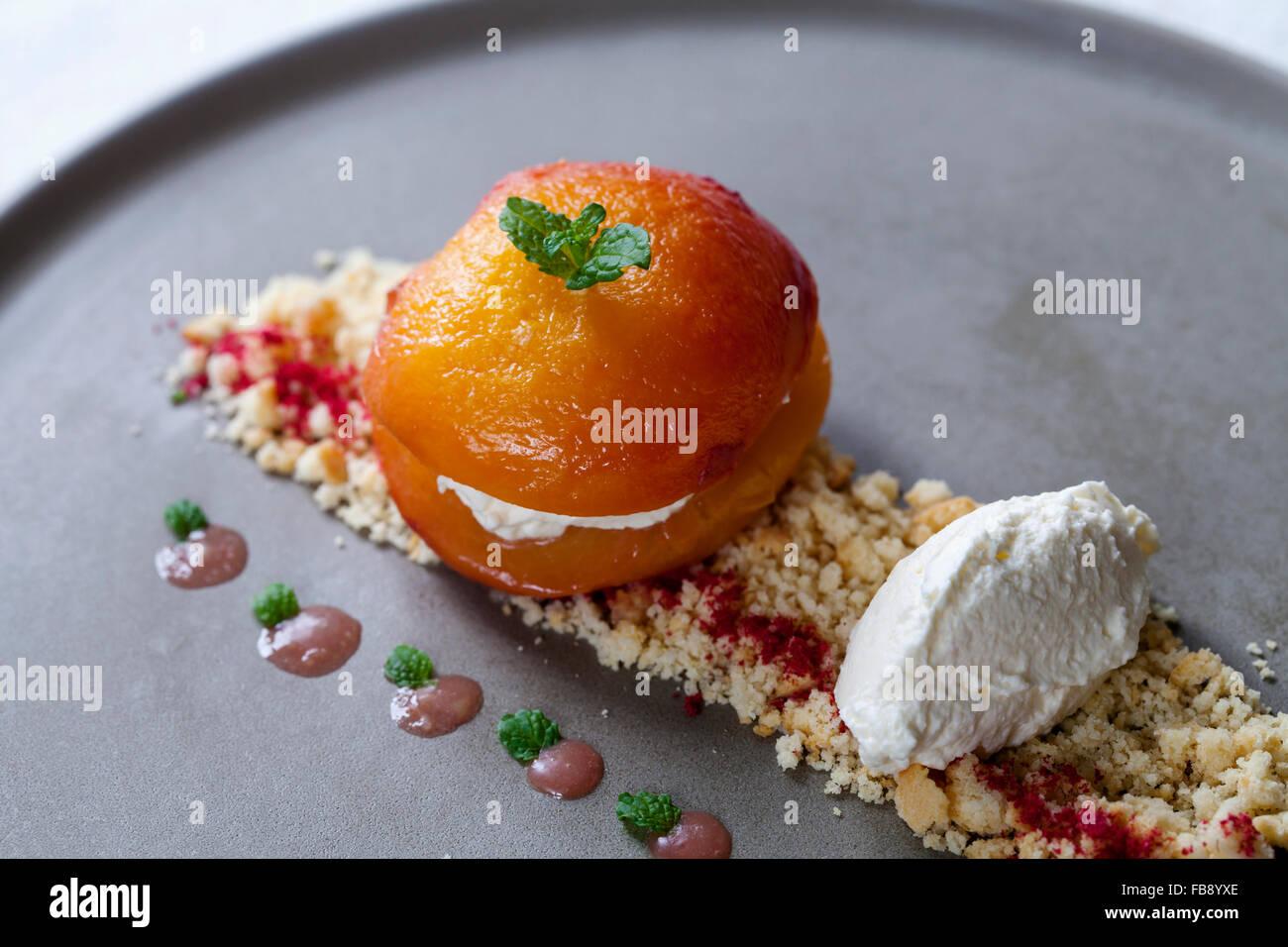 Roast Pfirsich mit Rahm, zerbröckelte Biskuit und Himbeer Pulver Stockbild