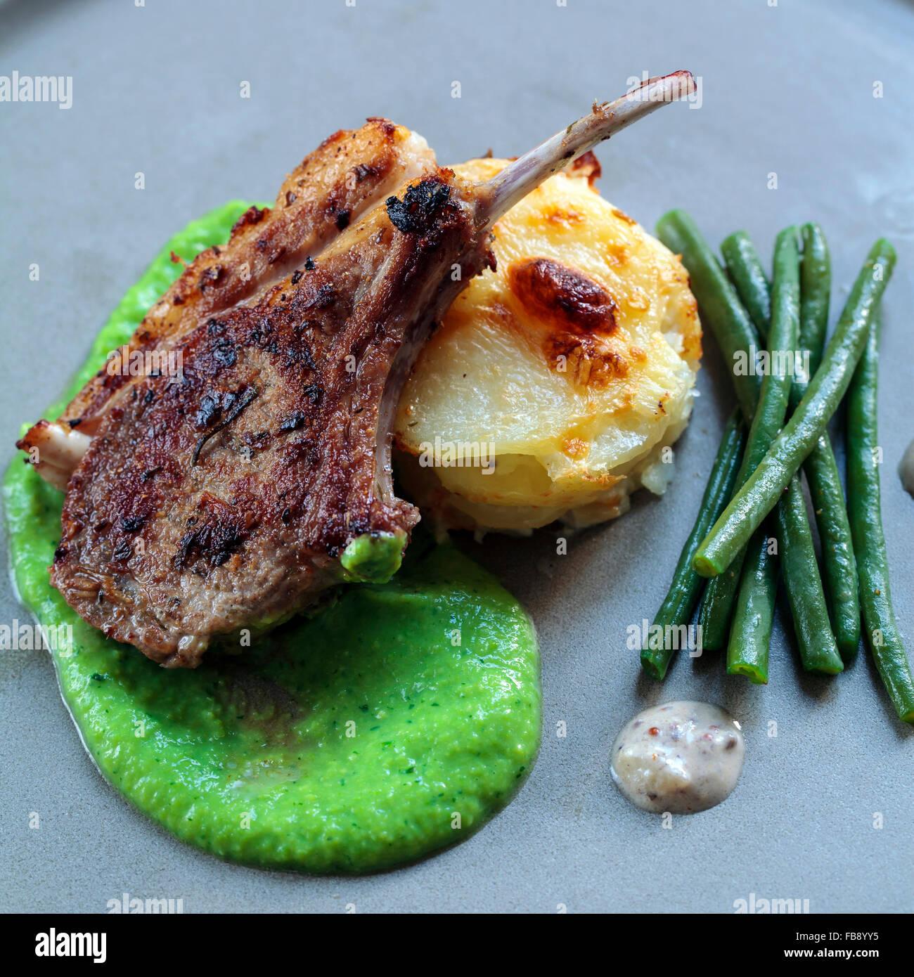 Lammkotelett mit Erbsen-Püree und Dauphinoise Kartoffeln Stockbild