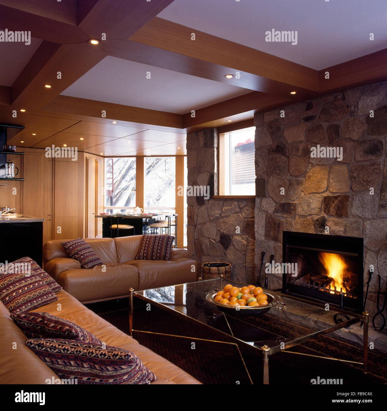 Beige Leder-Sofas und Kamin in rauen Steinwand im offenen ...