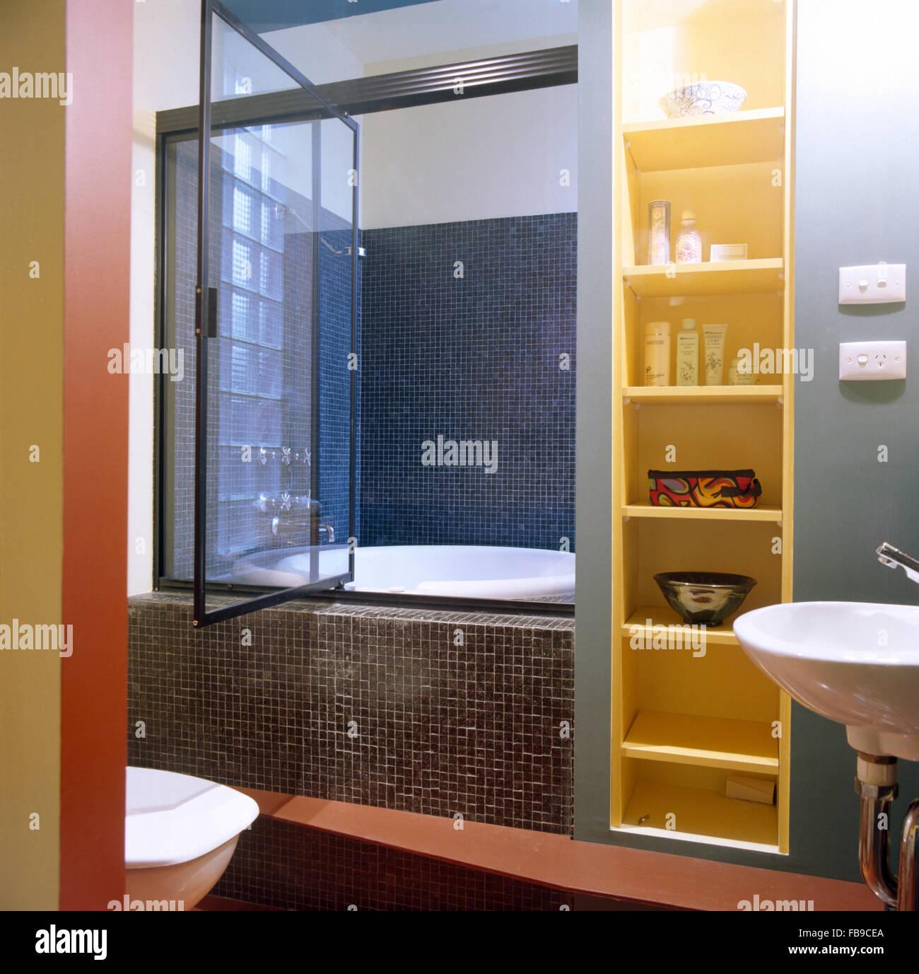 Schmales Regal neben Bad mit einer Dusche Tür und grau ...